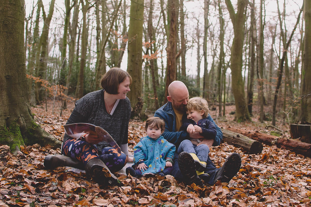 family cuddle up forest sharing book