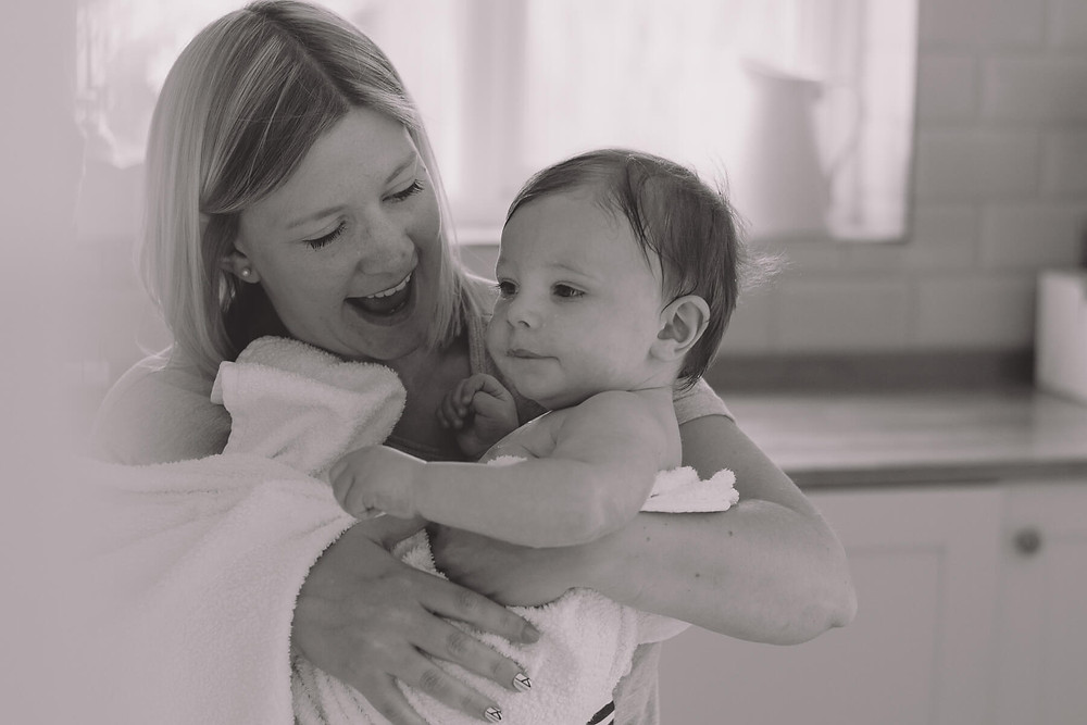 mum laughs carrying baby son wrapped in towel black white