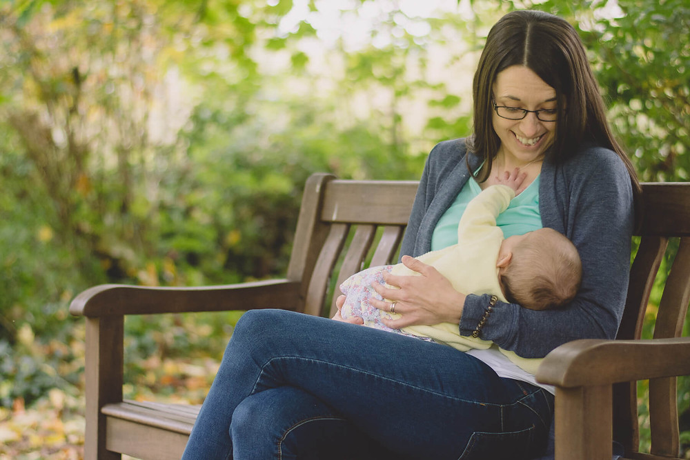 woman smiling in garden breastfeeding baby