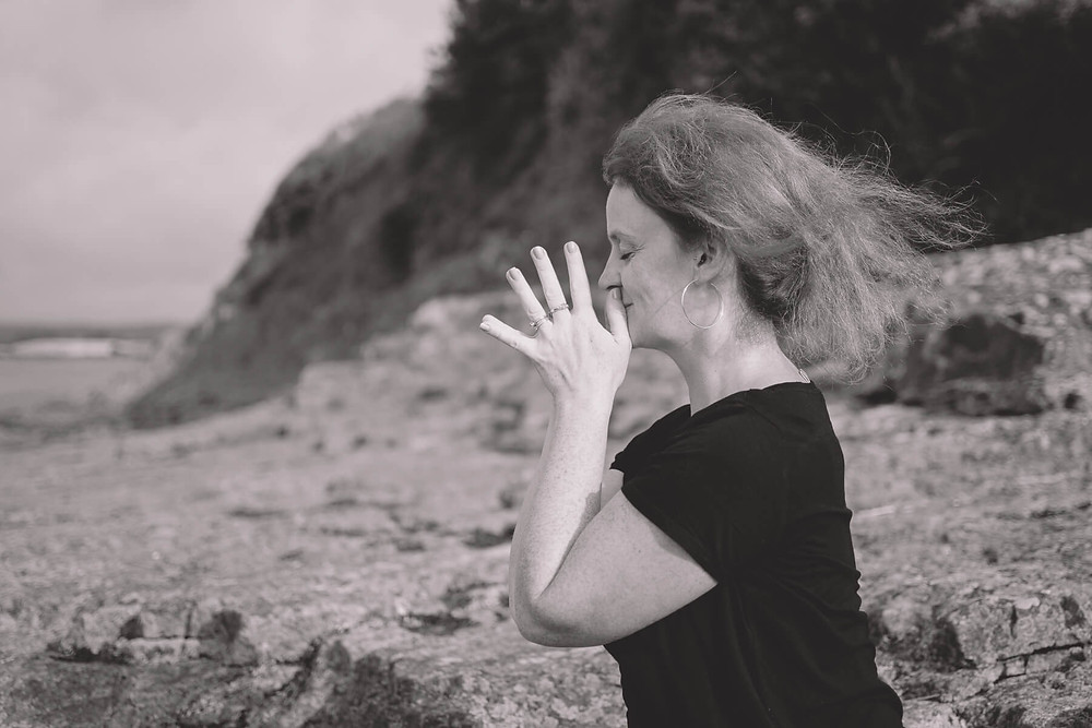 woman meditate on rocks by water