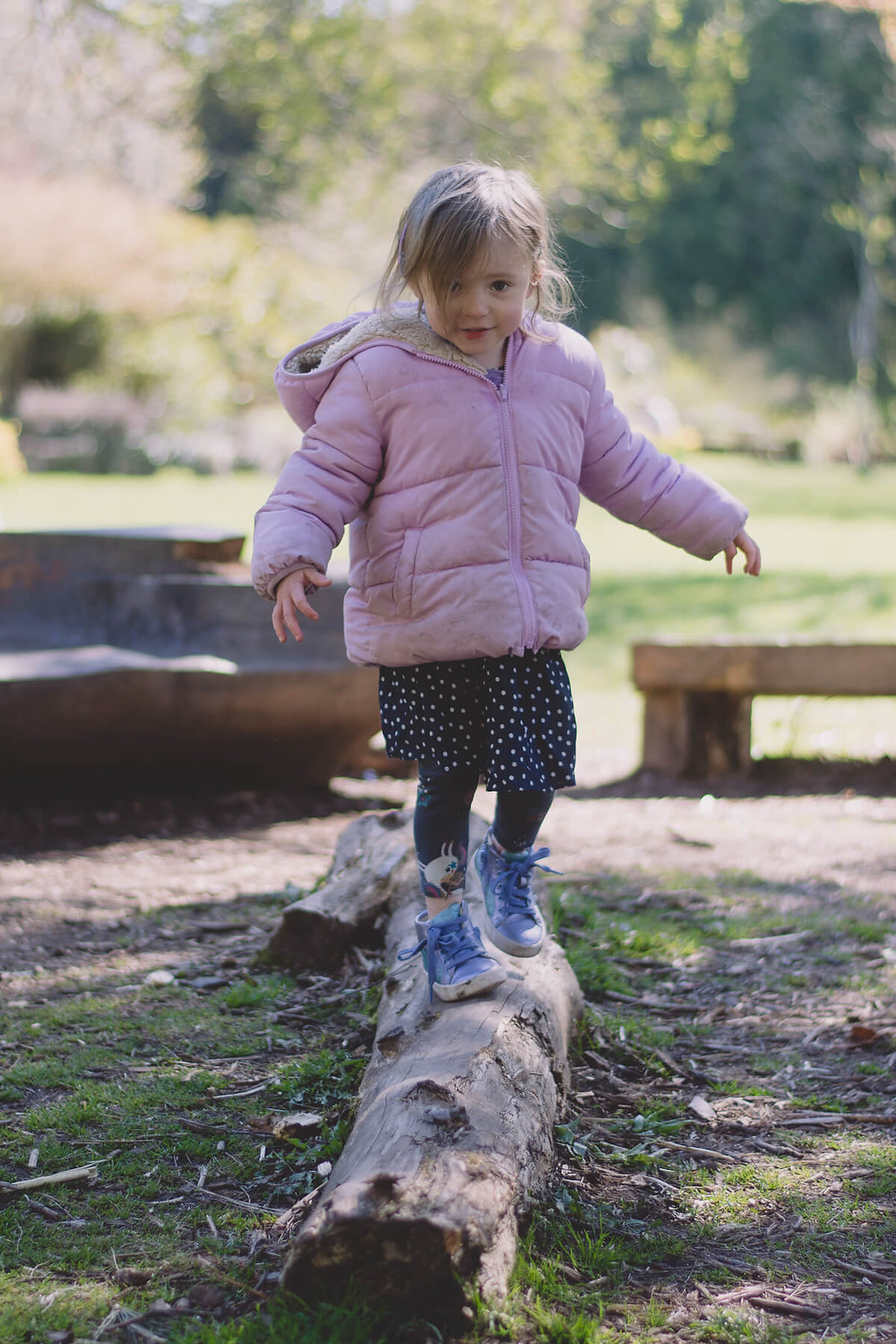 young girl pink coat playing in park balancing on log
