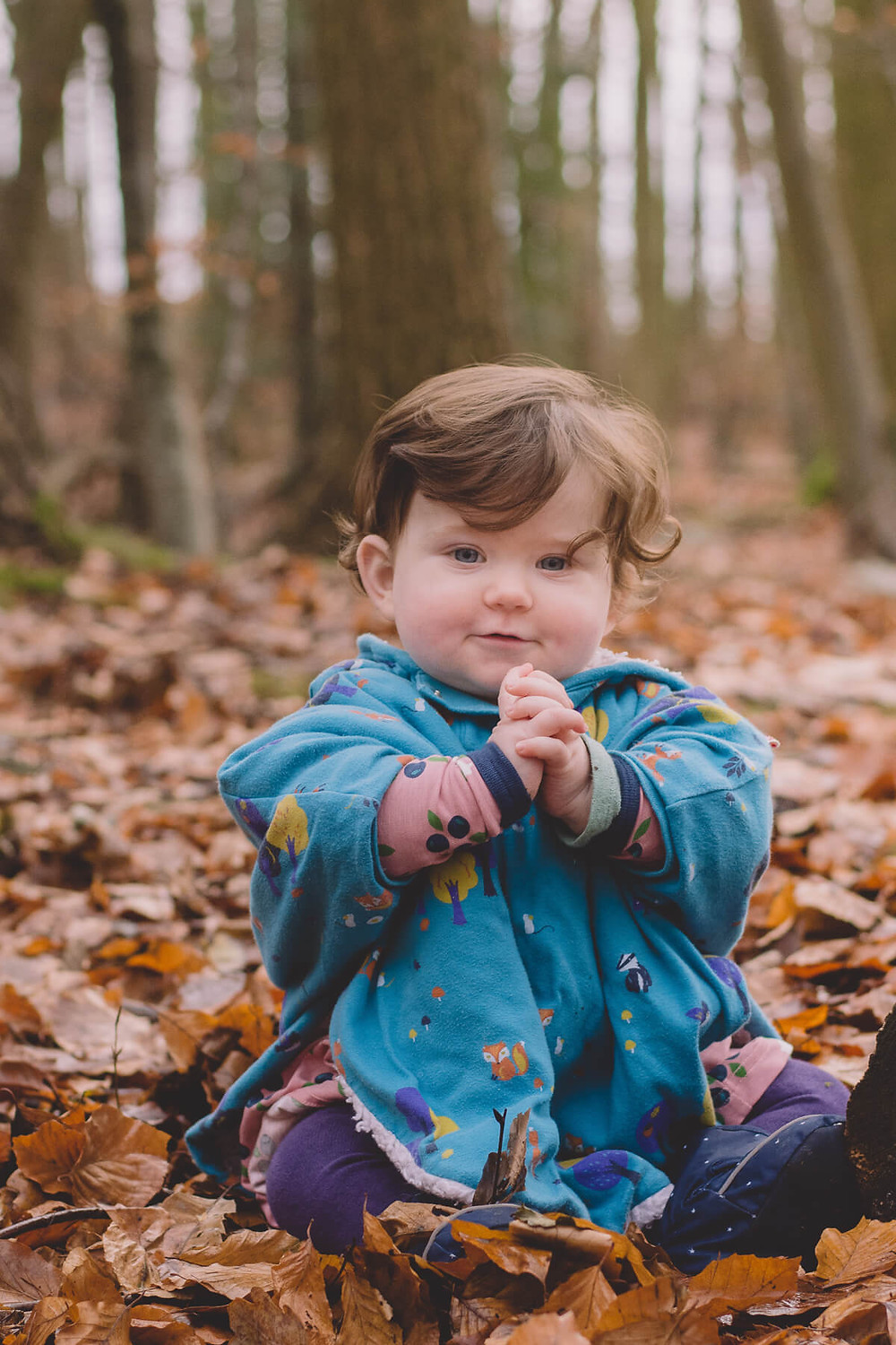 baby girl sitting on forest floor clapping hands sunny
