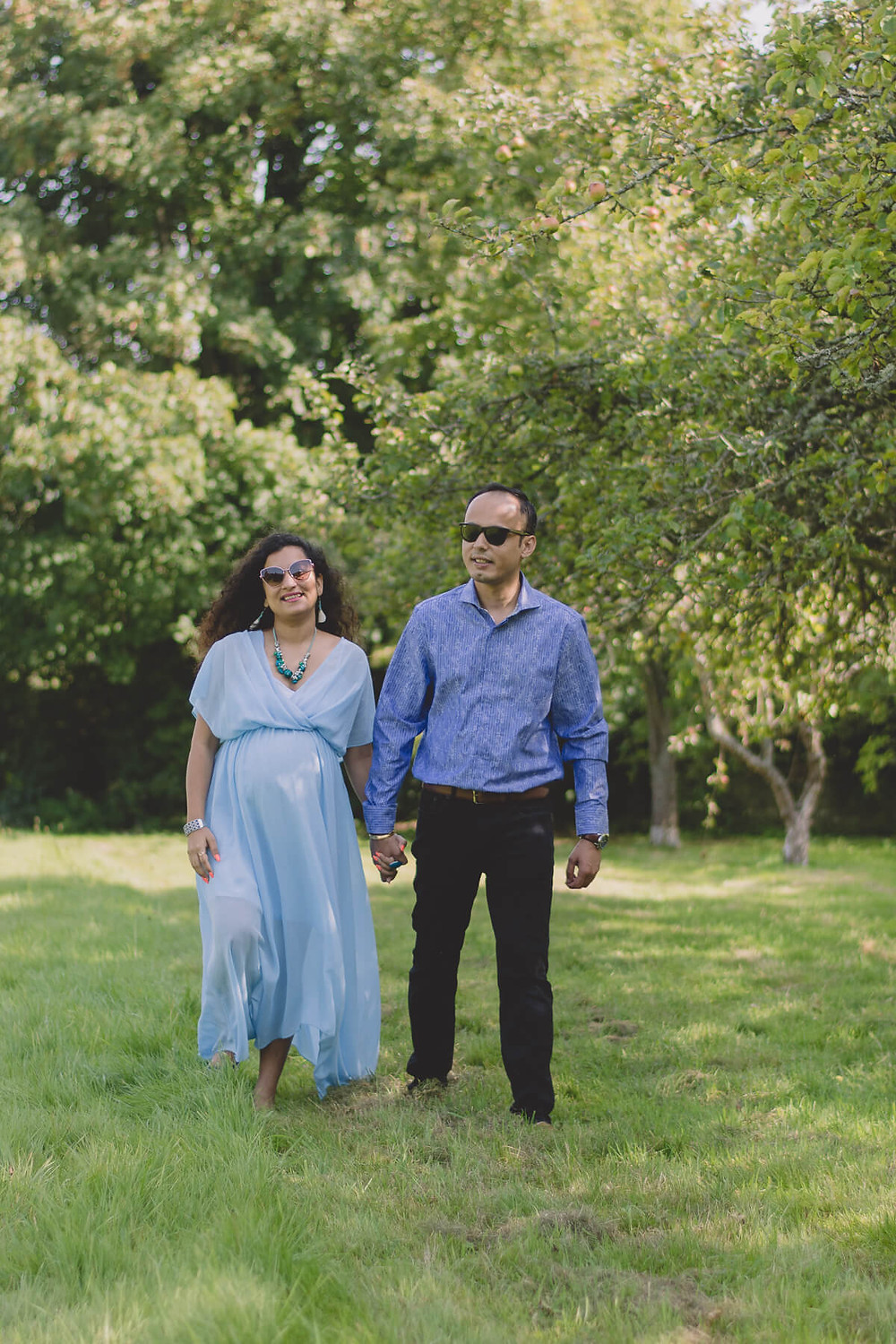 husband and pregnant wife walk through trees