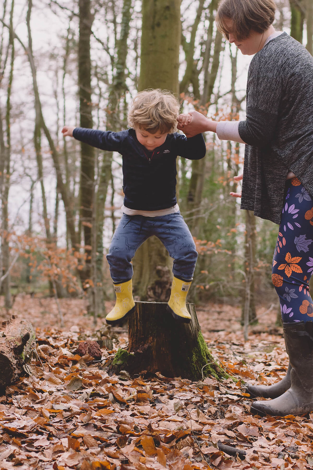 boy jumping off tree stump holding mums hand south wales