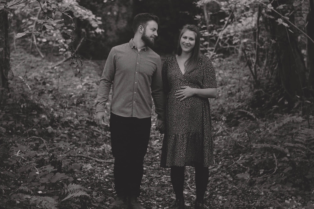 husband and pregnant wife stroll through woods