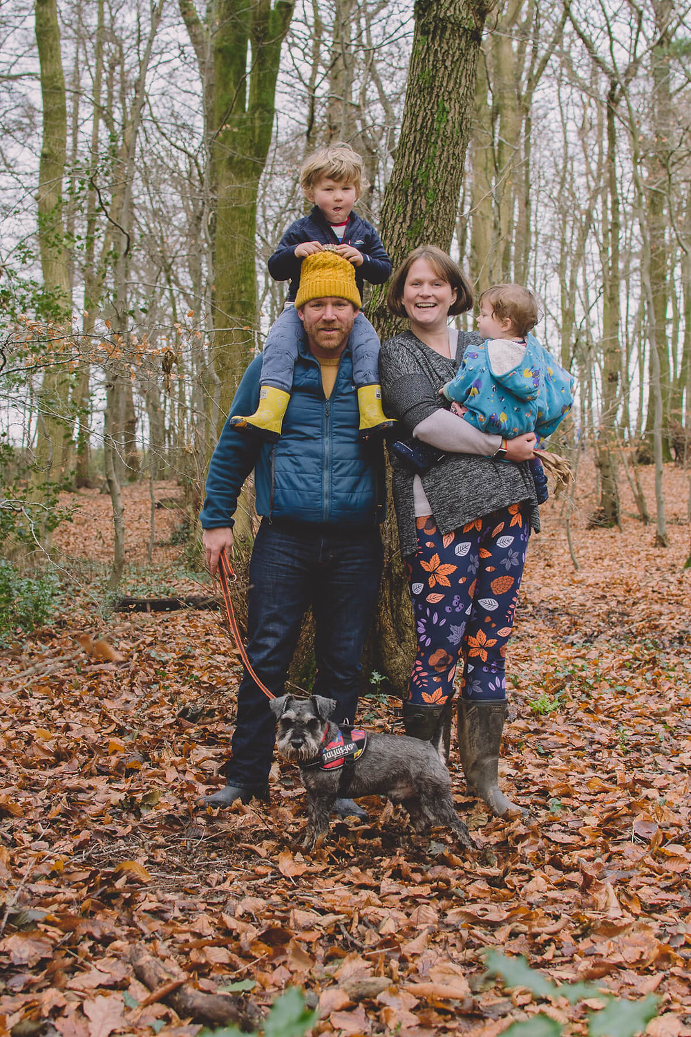family smiling in forest autumn with dog children playing