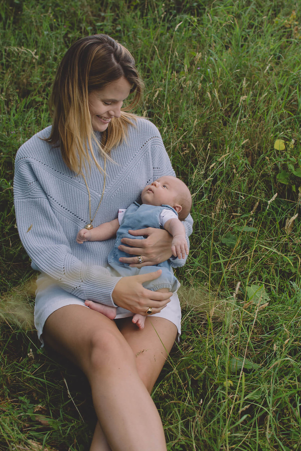 young mother sitting in grass smiling down on newborn baby