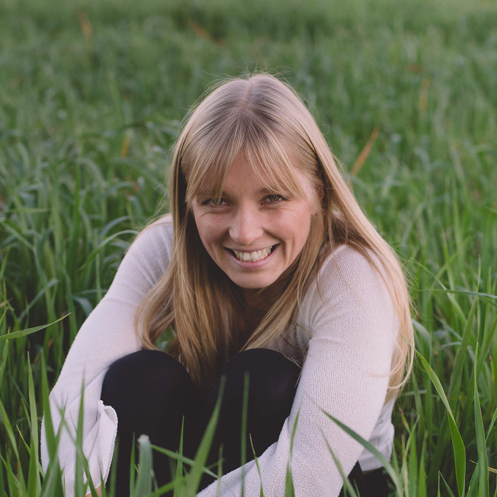 woman laughing sat in long green grass south wales monmouth