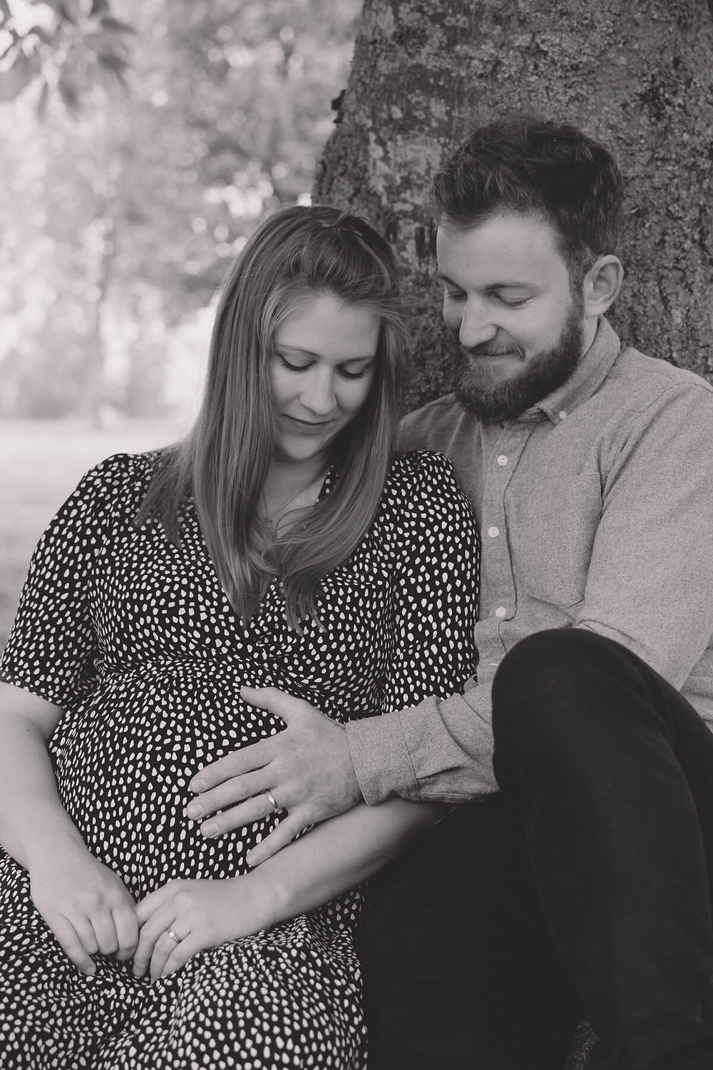 couple smiling hold pregnant bump outdoors