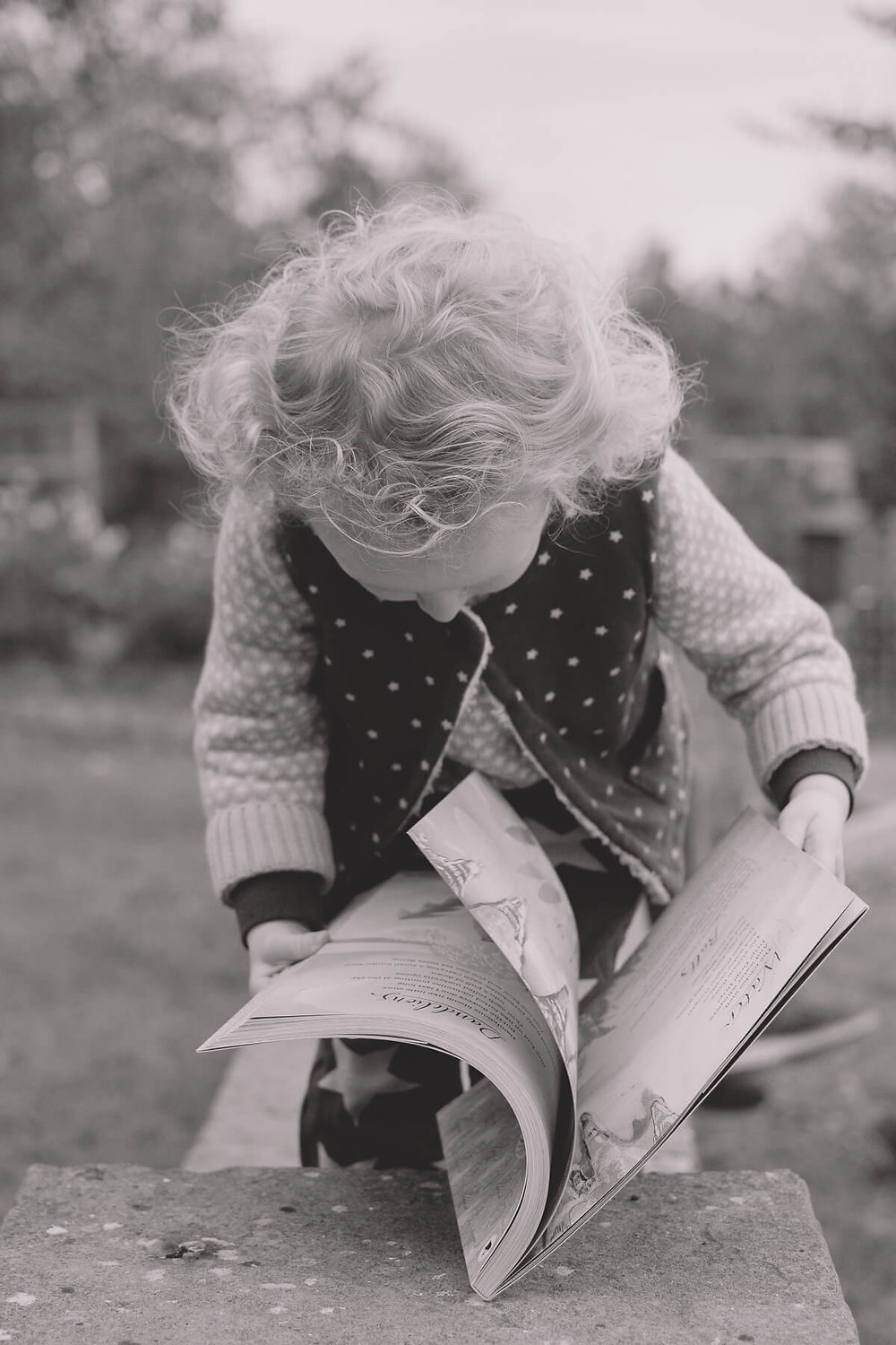 toddler reading book outside stone wall