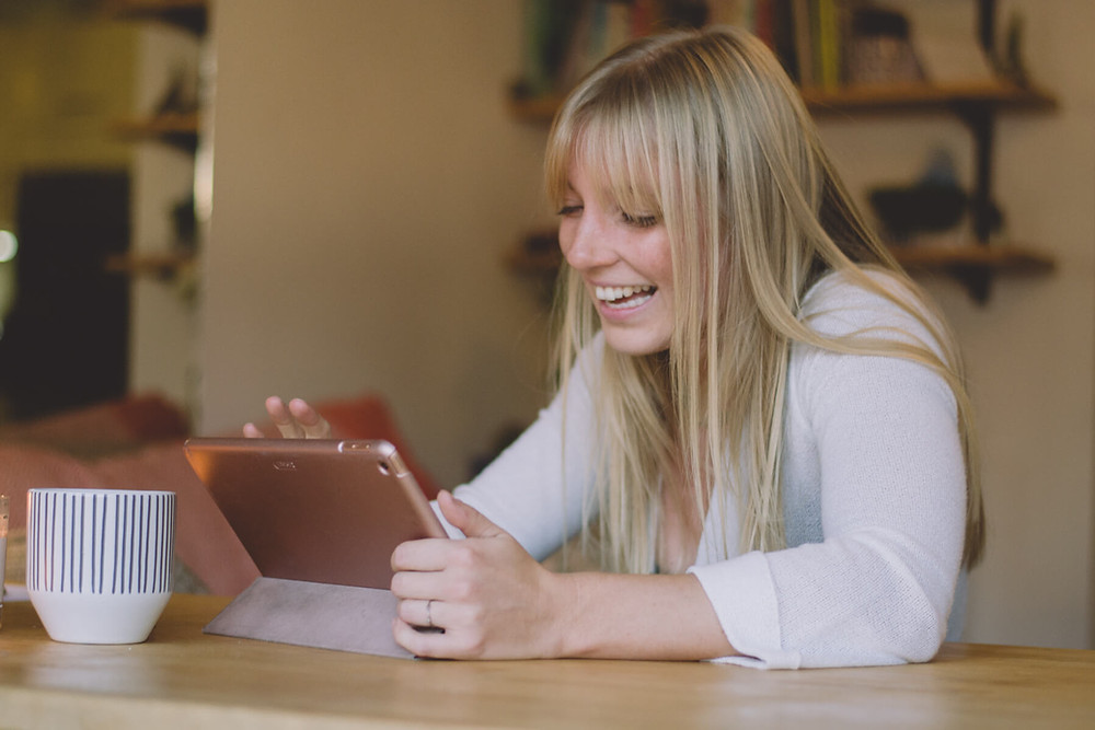 small business owner working at home on ipad laughing