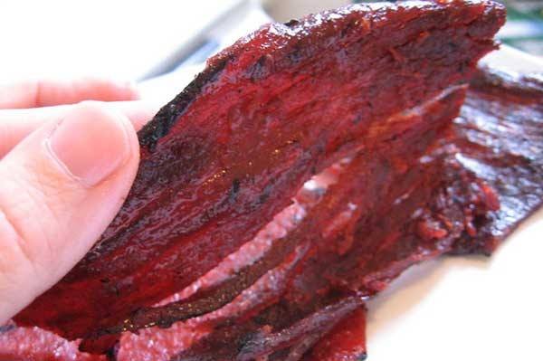 image showing a person checking beef jerky for its quality