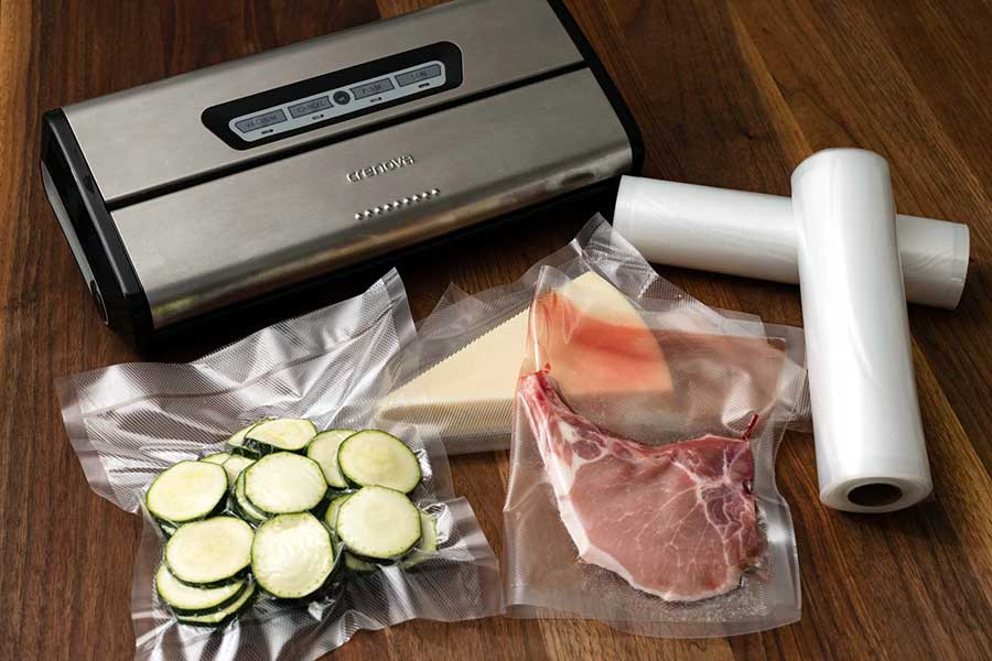 a vacuum packing machine with meats and vegetables inside packs