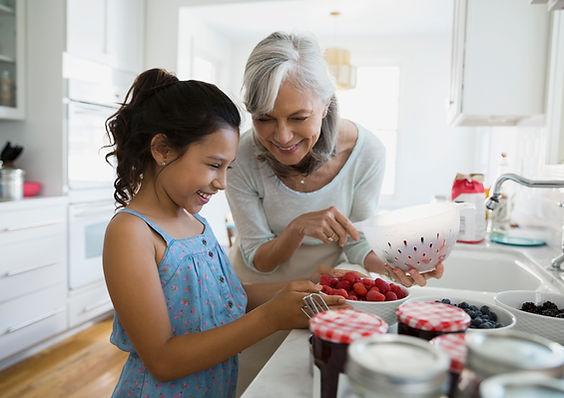 Grandma making raspberry jam with her granddaughter