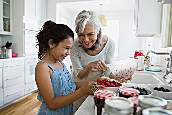 smiling grandma with smiling grandchild in kitchen, making Bonne Maman jam, with raspberries in ceramic bowl, blueberries in ceramic bowl, and blackberries in another, with kitchen sink faucett in background, and white kitchen cabinets in background. granddaughter is wearig lovely patterned blue dress, grandma wearing beige top and has sprawling white hair with hints of black, and a diamond ring