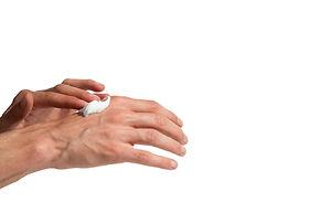 Young man applying hand cream iStock-637