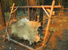A hide in a frame for rawhide. The beautiful lighting is due to smoke clouds from nearby forest fires, not dusk