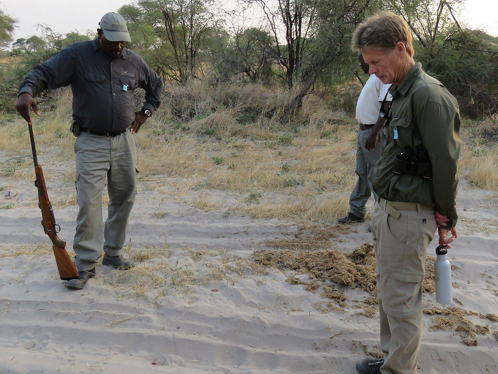 Emmanuel (left) inspecting snake tracks in the sand - photo by Debra Noell