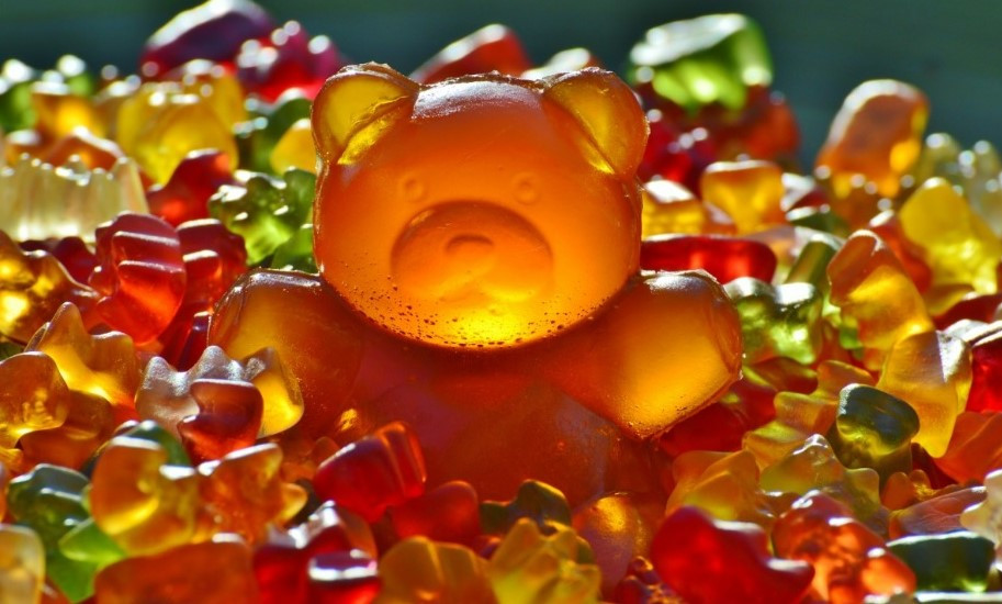 orange gummy bear in a pile of other colors