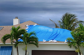 A damaged roof covered in a blue tarp symbolic of wind damage relevant to wind mitigation