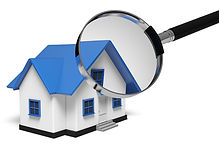 A model of a home beneath a magnifying glass symbolic of a home inspection