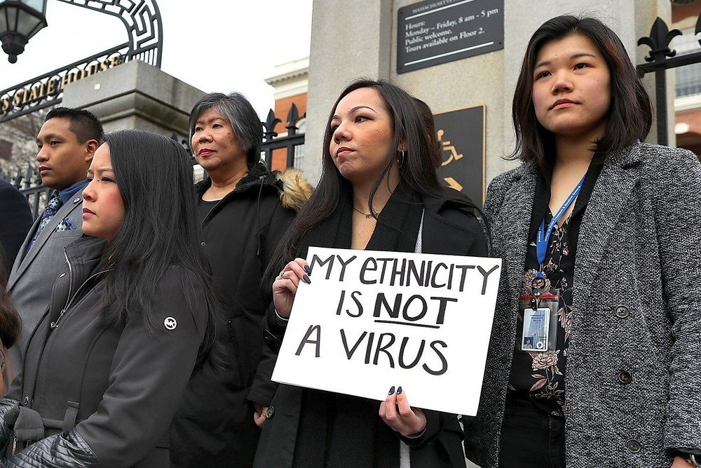 """Four protestors are pictured. One holds a sign that reads """"My ethnicity is NOT a virus"""""""