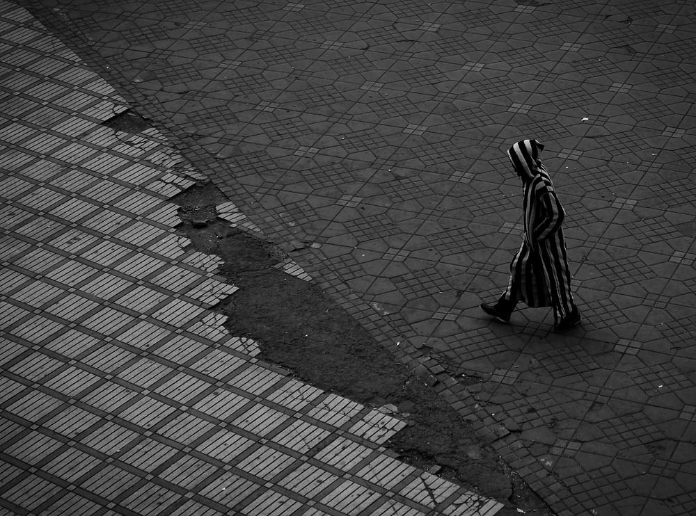 Photo by Noah Rosenfield on Unsplash - man in dressing gown walking down street