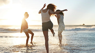 three-young-women-kicking-water-and-laug