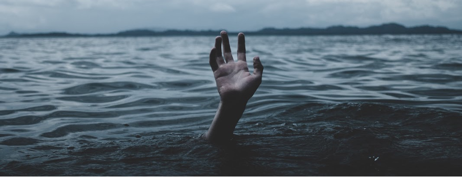 A hand rising from the water as someone drowns