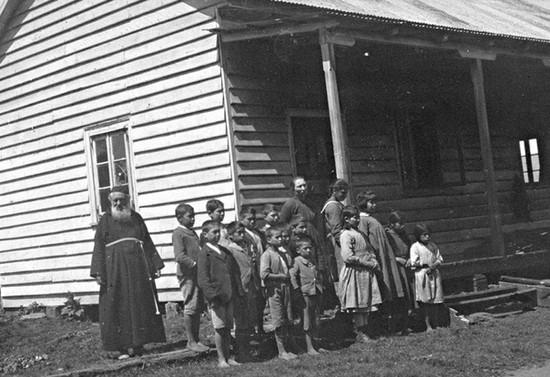 Padre Albuin y niños en escuela misional