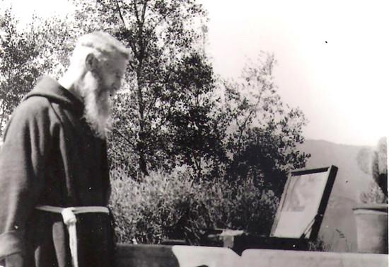 Padre Francisco observando una imagen sobre su caja de acuarelas. Década de 1940