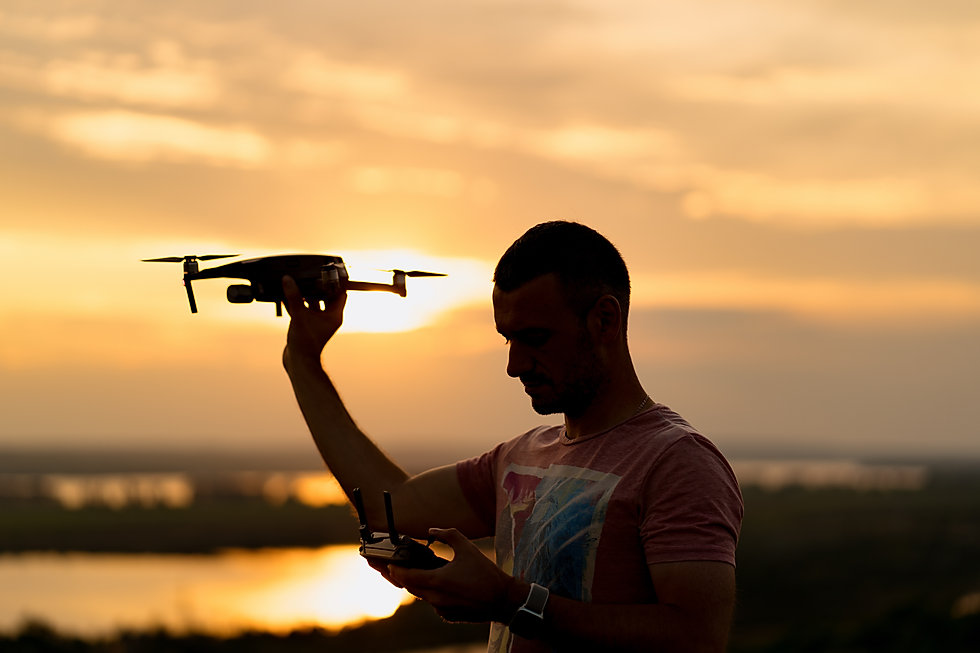 silhouette-of-man-piloting-a-drone-at-su