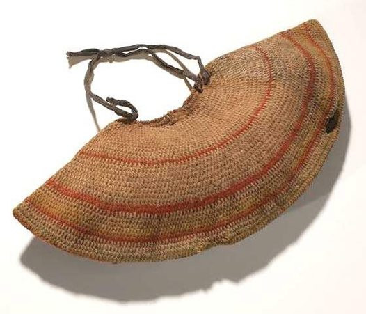 This is a yoke-shaped dilly bag from Boulia in south-western Queensland. It is made from woollen blanket thread and banded in green, orange and yellow with a navy and white polka-dotted cloth handle knotted onto the bag at diagonally opposite ends of the top opening. It is covered with the remnants of a red-brown ochre coating. It was collected in 1905 and feathers, plant matter and human hair were found inside it. It is 57 cm in width by 22 cm in length.