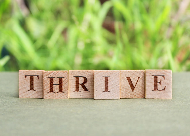 thrive. words on wood tiles with thrivin