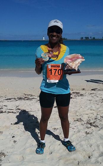 Dr. Marilyn at the finish line of Marathon Bahamas, Junkanoo Beach, Nassau, The Bahamas, with her awards.