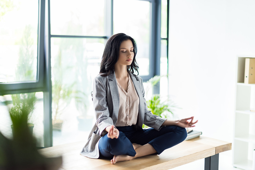 A beautiful woman meditating on the office desk