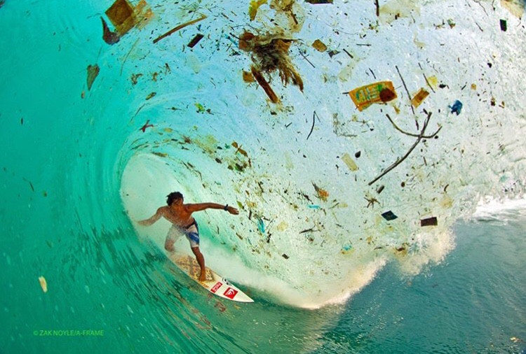 A surfer riding a wave full of plastic trash