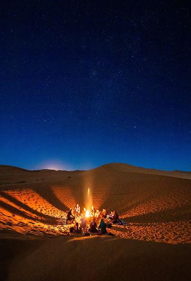 people-sitting-in-front-of-bonfire-in-de