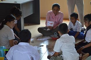 Cambodian teacher sitting on the floor with children.jpg