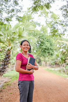 Cambodian woman standing on dirt road sm