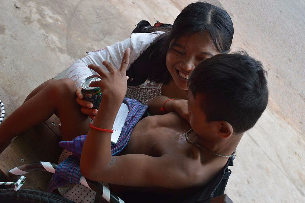 Cambodian women kneeling down and smiling as she interacts with a Cambodian boy in a primitive wheelchair with a kroma scarf as a seatbelt.
