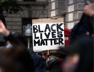 Image of hands holding a Black Lives Matter sign in a crowd