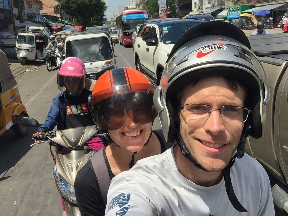 Mick & Jennie smiling riding a moto in traffic