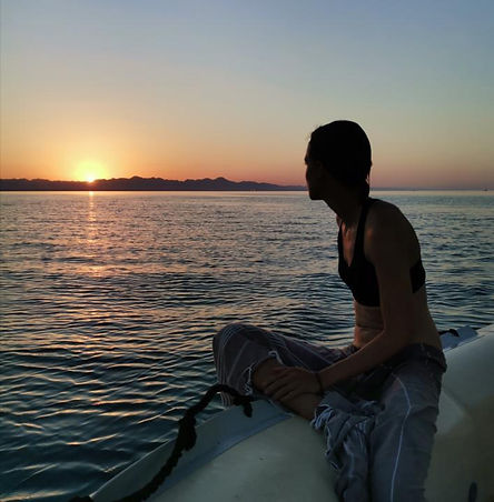 A girls watches the sunset behind a mountain range sitting on the edge of a motorboat