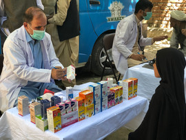 Mobile clinic staff providing information about medicines to young girl in rural parts of Nangarhar province in Afghanistan
