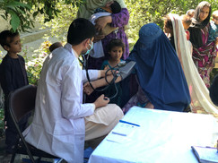 Mobile clinic staff checking a women's blood pressure in rural part of Nangarhar province in Afghanistan