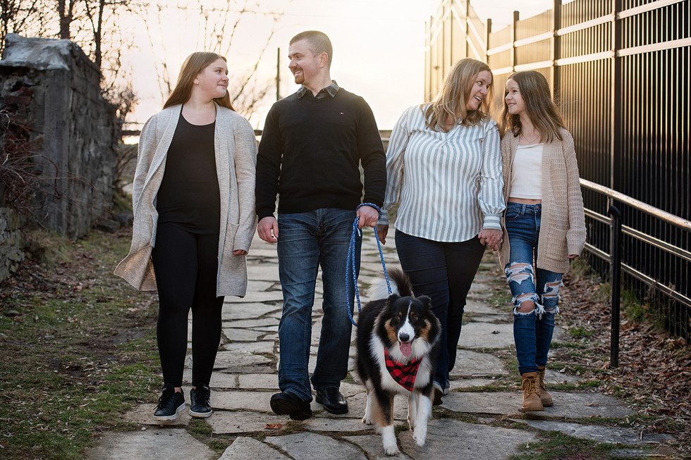 Family of four walking with dog