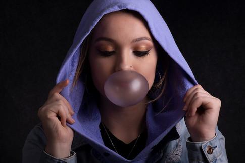 Studio portrait of girl blowing bubble