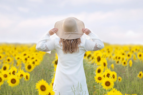 Blonde woman with hat in sunflowers