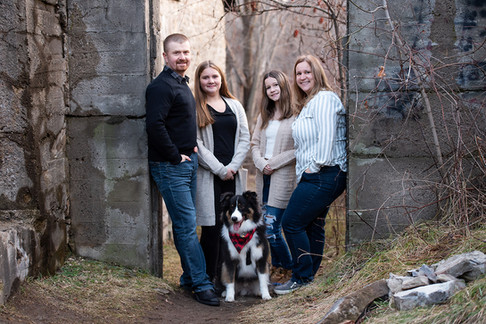 Family of four posing with dog